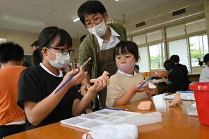 尾崎人形保存会の城島正樹さんにアドバイスを受けながら、絵付けをする西郷小の児童=神埼市の西郷小