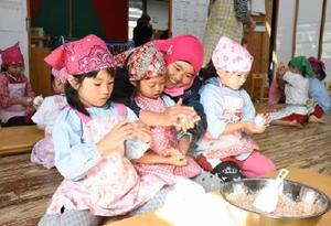 農業研修生の手を借りながら、おにぎりの形を整える園児=佐賀市大和町の保育園ひなた村自然塾