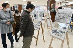 東日本大震災や佐賀豪雨のパネルを見つめる来場者=佐賀市のモラージュ佐賀
