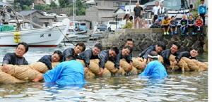 直径約40㌢の綱を抱くようにして引く男衆=唐津市鎮西町の波戸漁港