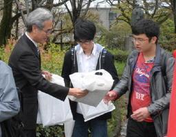 スタッフから新聞やリーフレットの入った袋を受け取る大学生=佐賀市本庄町の佐賀大学