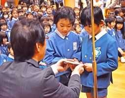 NTTドコモ佐賀支店の北村和喜支店長(左)から目録を受け取る園児たち=佐賀市若宮の三光幼稚園