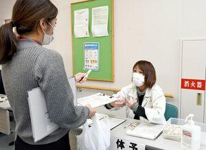 新型コロナウイルスのワクチン接種に向け、住民役の職員(手前)に予診票を配り、手順を確認する職員=江北町の保健センター