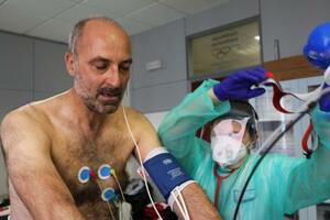 新型コロナウイルスに感染し退院後も体調不良が続く人を対象にしたリハビリ施設で、運動する元患者の男性(左)=7月22日、イタリア・ジェノバ(ゲッティ=共同)