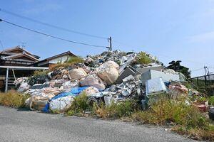 県による撤去命令の期限を過ぎても無造作に積まれたままの産業廃棄物=13日、神埼市千代田町