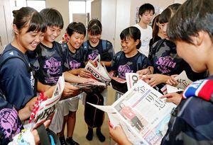佐賀新聞社が発行した特集紙面に見入る高校生=小城市の芦刈文化体育館