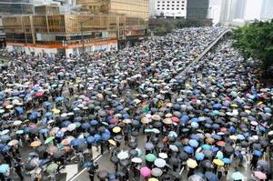 「逃亡犯条例」改正案の撤回を求め立法会周辺の道路を埋める市民ら=12日、香港(共同)