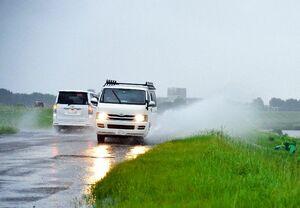 大きな水しぶきを上げながら行き交う車=24日午前7時25分ごろ、鳥栖市下野町