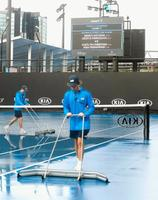 雨のため女子ダブルスの試合開始が遅れている全豪オープンの屋外コート=メルボルン(共同)