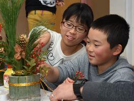 松などを差し込み、仲良く門松づくりを楽しむ子どもたち=吉野ヶ里町の三田川児童館