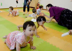 ゴールを目指し、ハイハイで元気に進む赤ちゃん=佐賀市新栄東の佐賀総合住宅展示場「イエス」