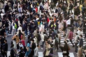 東京・渋谷のスクランブル交差点をマスク姿で歩く大勢の人たち=21日午後