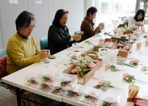東日本大震災と熊本地震で被災した小学校に贈ろうと開催したコサージュの制作会=佐賀市のアバンセ