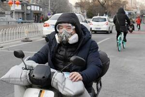マスク姿でバイクに乗る市民=18日、北京(共同)