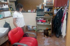 21日の大雨で浸水した美容室で片付け作業をする女性=22日午後、福岡県久留米市