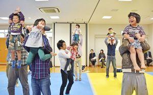抱き上げたり肩車をしたり体を動かしながらふれあう父親と子ども=神埼市の千代田町保健センター
