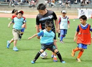 サガン鳥栖のアカデミーコーチ(中央)と共にミニゲームで汗を流す子どもたち=鳥栖市陸上競技場