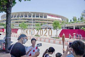 東京五輪の開会式の会場になるオリンピックスタジアム(新国立競技場)。聖火ランナーのユニホームを着た男性を海外メデイアが取材していた=22日、東京都内