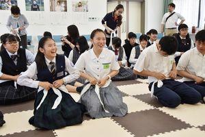 応急手当てに使う三角巾の使い方を学ぶ高校生=佐賀市の日赤県支部