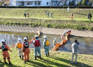 油流出事故に備え、オイルフェンスを張る訓練をする関係者=武雄市の武雄川