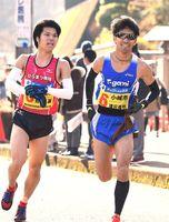 累計首位を守った小城市。溝田槙悟選手(右)が野中誠選手からたすきを受けて走り出す=武雄高校前