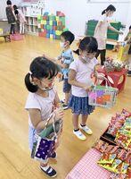 新聞紙を使った手作りエコバッグで夏祭りに買い物する園児たち=唐津市鎮西町の打上保育園