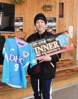 大会で優勝し、賞品だったサッカーJ1・サガン鳥栖のトーレス選手のサイン入りユニホームを手にした吉村和也さん