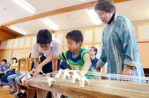 中学生に教わりながら筝を練習する児童=佐賀市の小中一貫校校富士校中学部
