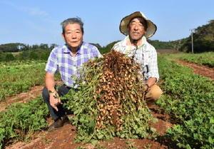 一株でこんなに。掘ったばかりの落花生を手に櫻井英敏さん(左)と福永隆司さん