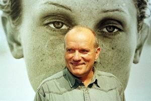 自身が撮影したモデルの写真の前に立つ生前のリンドバーグさん=1月下旬、ドイツ北部ハンブルク(ロイター=共同)