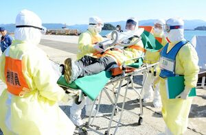 患者役の男性(中央)を緊急車両に運ぶ医療関係者。防護服を着て対応した=唐津市東大島町の唐津東港