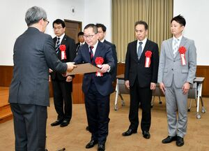 田中裕之局長(左)から賞状を受け取る功労団体賞の受賞者=佐賀県庁