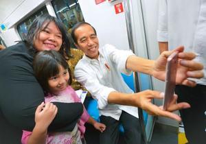 日本の支援で建設された都市高速鉄道(MRT)を視察し、車内で乗客との記念撮影に応じるインドネシアのジョコ大統領(右)=25日、ジャカルタ(共同)
