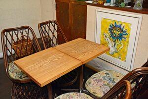 移転時、彫塑作家たちが旧店舗にあった黒いテーブルの塗装をはがして木目調に。奥の絵は古賀悦子さんの作品