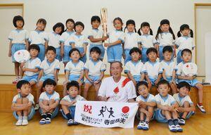 三根みどり保育園で園児たちと記念撮影に収まる寺田恭夫さん