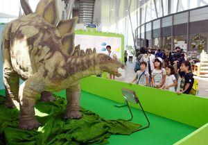 首を振り叫び声を上げる6メートルのステゴザウルスのロボットを見入る子どもたち=武雄市の宇宙科学館
