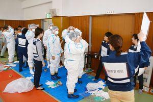 鳥インフルエンザの防疫演習で、防護服の着用の仕方を確認する参加者=佐賀市川副町のスポーツパーク川副武道場