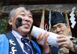 宮城県石巻市長面地区の奇祭「アンバサン」で、大根に塗られたすすを付けられ笑顔の男性=10日午後