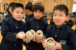 大きく育ったカブトムシの幼虫をもらい、笑顔を見せる児童たち=太良町の大浦小学校
