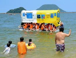 筑肥線と唐津線の車両を模したイカダと、浅瀬から声援を送る観客=唐津市の西の浜