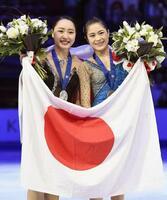 2018年3月、フィギュアスケートの世界選手権で、日の丸を手に笑顔を見せる銀メダルの樋口新葉(左)と銅メダルの宮原知子=ミラノ(共同)