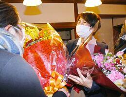 支持者から初当選を祝う花束を受け取り、涙ぐむ久保美樹さん=1月31日午後11時半ごろ、唐津市の中町Casa