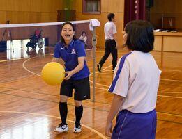 ソフトバレーボールを使ったスパイクの練習を手伝う座安琴希選手(左)=みやき町の中原特別支援学校