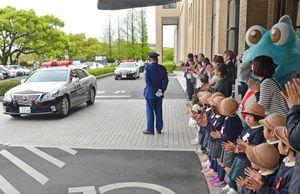 春の交通安全県民運動の出発式で、巡回に向かうパトカーを見送る園児たち=県庁