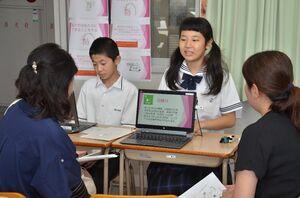 SDGsの各目標について、来場者に向けてプレゼンテーションをする生徒たち=佐賀市の龍谷中