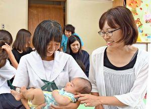 赤ちゃんを大切に抱く女子生徒=鳥栖西中