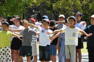 全員で出演するシーンを撮影する子どもたち=佐賀市城内の佐賀県立図書館前広場