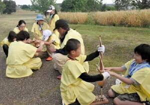 力を合わせて火おこしに挑戦する参加者=吉野ケ里歴史公園