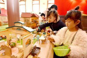 動物のドールハウスシリーズ「シルバニアファミリー」で楽しむ子どもたち。幼少期に遊んだ30代の母親と来場していた=佐賀市の旧古賀銀行