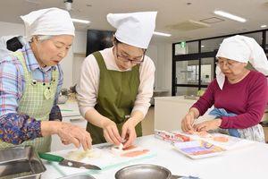 手際良く具材を切ったり、新玉ねぎに肉を巻いたりする参加者たち=佐賀市の佐賀メディカルセンタービル